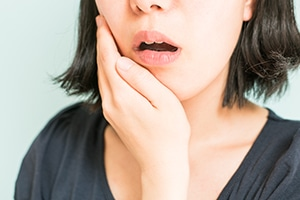 Woman experiencing tooth ache holding her cheek